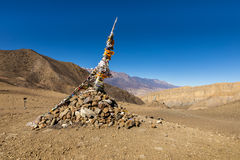 Traditional tibetan pile of stones and colored flags Royalty Free Stock Images
