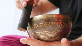 Traditional Tibetan Singing Bowl. Man Playing on Bronze Meditation Bowl Calm Sounds for Good Energy and Health. 4K. Slowmotion stock video footage