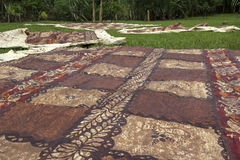 Traditional Tongan tapa. Drying on the grass stock photo