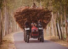 Traditional tractor vehicles with passengers running in an urban road of Bangladesh. People are travelling on a traditional vehicle in the urban road isolated royalty free stock photo
