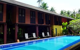 Traditional Tropical resort & swimming pool. A photograph showing a beautiful wooden house in the traditional architectural style of tropical Malaysia, built Stock Image