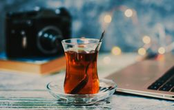 Traditional tulip tea glass with black tea on the wooden desk with computer and a black retro camera on the background. Traditional Turkish tea glass on the royalty free stock images