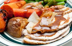 Traditional turkey dinner with crispy skin, turkey slices and fr Royalty Free Stock Photography