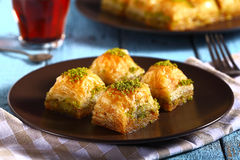 Traditional turkish baklava with tea on a blue background. Traditional turkish baklava with tea stock image