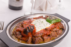 Traditional Turkish Bursa Iskender Kebap Garnished with Grilled. Traditional Turkish Bursa iskender kebap doner served with special red sauce and yogurt in the Royalty Free Stock Photo