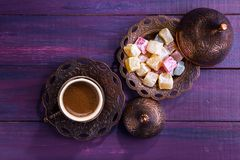 Traditional turkish coffee and turkish delight on dark violet wooden background. Flat lay.  stock images