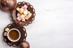 Traditional Turkish coffee and Turkish delight on white shabby wooden background. Top view.  stock images