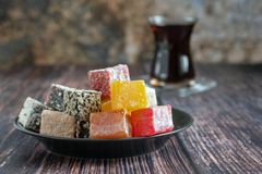 Traditional turkish delight and glass for tea bardak on dark wooden background royalty free stock photos