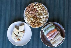 Traditional Turkish Delight. Oriental dessert halva on a  plate. Isolated on background. Eastern delicacy sweets. Healthy food. Nuts mix assortment. Collection stock photography