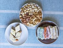 Traditional Turkish Delight. Oriental dessert halva on a  plate.  on background. Eastern delicacy sweets. Healthy food. Nuts mix assortment. Collection of royalty free stock image