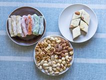 Traditional Turkish Delight. Oriental dessert halva on a  plate. Isolated on background. Eastern delicacy sweets. Healthy food. Nuts mix assortment. Collection royalty free stock photos