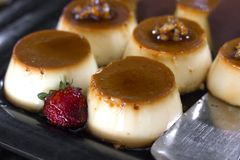 Traditional Turkish dessert - cream caramel, decorated with fresh strawberries, on a black tray stock image