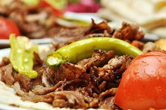 Traditional Turkish doner kebab with grilled vegetables. Doner kebab is a Turkish kebab, made of meat cooked on a vertical rotisserie. Seasoned meat stacked in stock photo