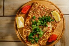 Traditional Turkish food Lahmajun on a wooden tray. royalty free stock images
