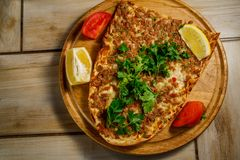 Traditional Turkish food Lahmajun on a wooden tray. View from above stock photography