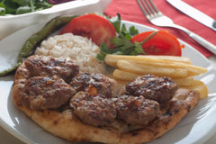 Traditional Turkish  grilled meatballs. Served with rice, fried chips, flat bread and grilled peppers and tomatoes Royalty Free Stock Images