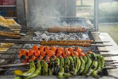 Traditional Turkish kebab with tomatoes and green peppers on bbq, outdoor royalty free stock photography