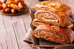 Traditional turkish pastry roll with chocolate and nuts filling. Pastich served on a vintage tray and dates on a wooden background Royalty Free Stock Image