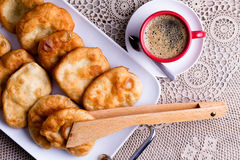 Traditional Turkish pisi halka or fried dough. Traditional Turkish pisi halka, or fried golden dough, served on a tray with a freshly brewed cup of frothy black Royalty Free Stock Photography