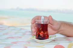 Traditional Turkish tea against the landsape. Traditional Turkish tea and man`s hand against the landsape Royalty Free Stock Photography
