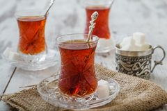 Traditional Turkish Tea. Turkish tea served in traditional glasses on white wooden background Royalty Free Stock Images
