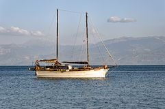 Two Masted Sailing Yacht Anchored in Bay, Greece. A traditional two masted sailing yacht, or boat, anchored for the night in the protected waters of a Gulf of Stock Photography