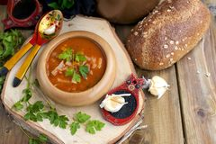 Traditional Ukrainian beet soup borscht in wooden bowl with garlic buns pampushka and dry cured pork belly on rustic wooden table stock photography