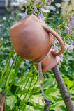 Traditional Ukrainian clay jug standing on a cut tree. Ancient traditional Ukrainian clay pot standing on a cut tree in summer garden Stock Image