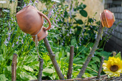 Traditional Ukrainian clay jug standing on a cut tree. Ancient traditional Ukrainian clay pot standing on a cut tree in summer garden Royalty Free Stock Photo