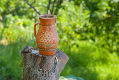 Traditional Ukrainian clay pot standing on a cut tree in summer garden. Ancient traditional Ukrainian clay pot standing on a cut tree in summer garden Stock Photography