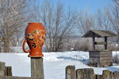Traditional Ukrainian rural landscape with a wooden well and fence with hanging pitcher on it with Petrykivka folk painting. Snowy winter day stock image