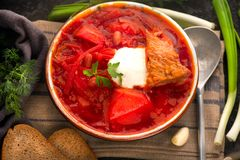 Traditional Ukrainian russian borscht. Plate of red beet root soup borsch on black rustic table. Traditional Ukrainian cuisine Stock Photo