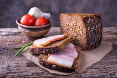 Traditional ukrainian sandwiches with brown rye bread, smoked la. Traditional ukrainian sandwiches made of brown rye bread and smoked lard on a piece of brown Stock Image
