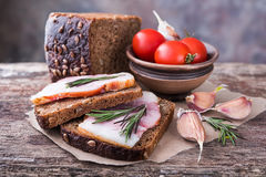 Traditional ukrainian sandwiches with brown rye bread and smoked. Traditional ukrainian sandwiches made of brown rye bread and smoked lard on a piece of brown Stock Photo