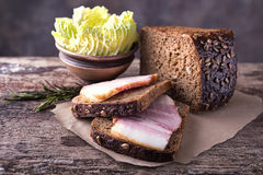 Traditional ukrainian sandwiches made of brown rye bread and smo. Ked lard on a piece of brown paper and natural wooden textured surface with unfocused Stock Image