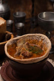 Traditional Ukrainian soup served in bread. Against the backdrop of a still life of a medieval Stock Photos