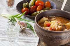 Traditional ukrainian vegetable soup - borsch, marinated tomatoes and cucumbers, sour cream, sliced bread, herbs and garlic Stock Photography
