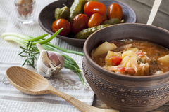 Traditional ukrainian vegetable soup - borsch, marinated tomatoes and cucumbers, sour cream, sliced bread, herbs and garlic Royalty Free Stock Images