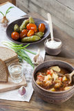 Traditional ukrainian vegetable soup - borsch, marinated tomatoes and cucumbers, sour cream, sliced bread, herbs and garlic Stock Photo