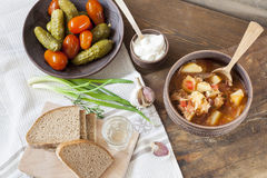 Traditional ukrainian vegetable soup - borsch, marinated tomatoes and cucumbers, sour cream, sliced bread, herbs and garlic Stock Image