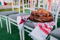 Traditional Ukrainian wedding bread loaf in wedding ceremony area. Wooden chairs for guests Royalty Free Stock Photo