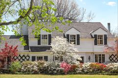 Traditional upscale home with dogwood tree and azelea bushes - b Stock Photos