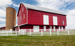 Traditional US red painted barn on farm. Red painted wooden barn with white door on farm in traditional US style Stock Images