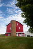 Traditional US red painted barn on farm. Red painted wooden barn with white door on farm in traditional US style Stock Photography