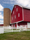 Traditional US red painted barn on farm. Red painted wooden barn with white door on farm in traditional US style Stock Photo