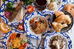 Traditional Uzbek dinner. Pilaf, manta, kebab, bread on the table with vegetables. Traditional Uzbek dinner. Plov, manta, kebab, bread on the table with Royalty Free Stock Photography