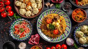 Traditional Uzbek oriental cuisine. Uzbek family table from different dishes in national dishes for the New Year holiday. The background image is a top view royalty free stock photography