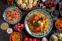Traditional Uzbek oriental cuisine. Uzbek family table from different dishes in national dishes for the New Year holiday. The background image is a top view royalty free stock photo