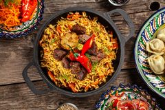 Traditional Uzbek oriental cuisine. Uzbek family table from different dishes in national dishes for the New Year holiday. The background image is a top view stock image