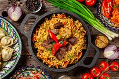 Traditional Uzbek oriental cuisine. Uzbek family table from different dishes in national dishes for the New Year holiday. The background image is a top view royalty free stock images